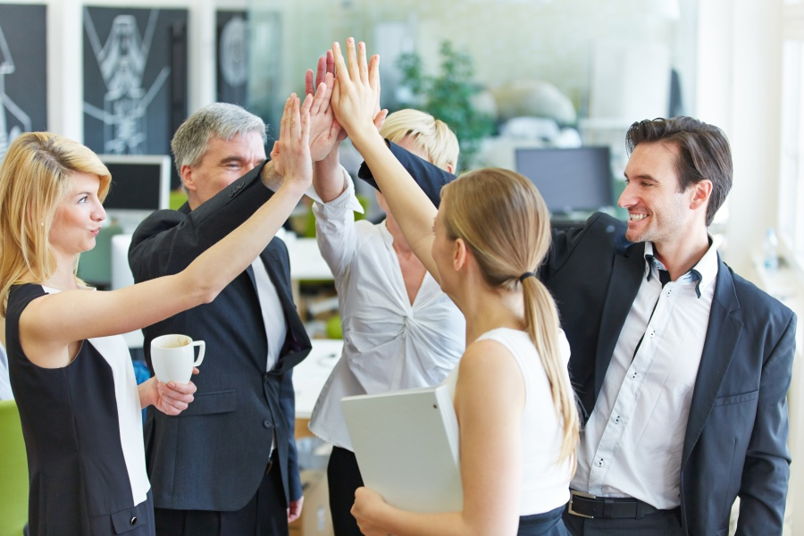 Business Team macht High Five im Büro